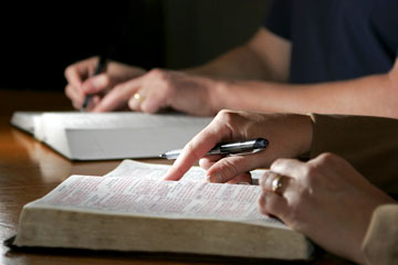 Couple studying the Holy Bible together at a table (shallow focus side lighting).