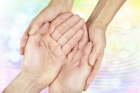 Female hands gently holding male hands in cupped position on a subtle rainbow colored water ripple background fading to white with plenty of copy space