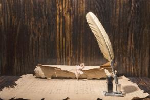 Vintage golden pen and ancient manuscripts on a wooden backgroun